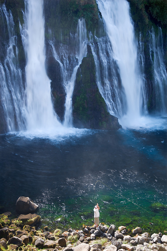 Fly fisherman with fish on at Burney Falls. McArthur-Burney Falls Memorial State Park, California