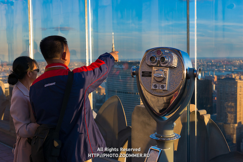 Chinese tourists on observation deck of Rockefeller Center watching Manhattan skyscrapers