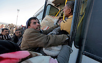 Men attempt to get on a bus taking them from a Tunisian border station. Thousands of people, mainly Egyptian workers, fled unrest in Libya and cross the border into Tunisia. Some slept in the open for several days before being processed. .At the same time forces loyal to Col. Gaddafi fought opposition forces in various parts of the country.