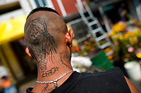 A Mexican follower of Santa Muerte (Saint Death) shows his tattoo outside the shrine in Tepito, a rough neighborhood of Mexico City, Mexico, 1 May 2011. The religious cult of Santa Muerte is a syncretic fusion of Aztec death worship rituals and Catholic beliefs. Born in lower-class neighborhoods of Mexico City, it has always been closely associated with crime. In the past decades, original Santa Muerte's followers (such as prostitutes, pickpockets and street drug traffickers) have merged with thousands of ordinary Mexican Catholics. The Saint Death veneration, offering a spiritual way out of hardship in the modern society, has rapidly expanded. Although the Catholic Church considers the Santa Muerte's followers as devil worshippers, on the first day of every month, crowds of believers in Saint Death fill the streets of Tepito. Holding skeletal figurines of Holy Death clothed in a long robe, they pray for power healing, protection and favors and make petitions to 'La Santísima Muerte', who reputedly can make life-saving miracles.