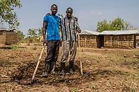 Okelo Atto aus dem Südsudan mit Jamal Babu (von links nach rechts) aus Uganda bei der gemeinsamen Arbeit im Flüchtlingslager BidiBidi in Uganda. Über eine Million Südsudanesen sind nach Uganda geflüchtet.
