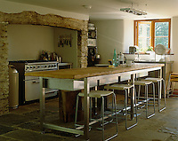 The deep recessed fireplace easily accomodates the huge cooker in this contemporary country kitchen