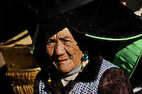 CHINA Yunnan , ethnic minority, Yi woman with a traditional decorated black hat / CHINA Provinz Yunnan , ethnische Minderheiten, Yi Frau mit schwarzem Hut