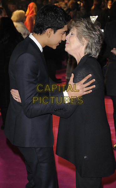 Dev Patel & Penelope Wilton.Arrivals at 'The Best Exotic Marigold Hotel' world premiere held at the Curzon Mayfair, London, England..February 7th, 2012.half length trousers top black blue suit brown tie side profile funny.CAP/CAN.©Can Nguyen/Capital Pictures.