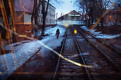 A woman walks on snow along a tram track in Oryol, a poor city in the heart of Russia.