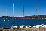 A catamaran anchored on the blue waters of Lake Coeur d Alene, Idaho, with smaller rentals on the beach.