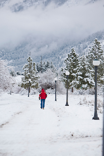 A man in a red coat walks along the riverfront path on a snowy winter day in Missoula, Montana