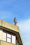 Antony Gormley human figure sculpture on rooftop, campus of University of East Anglia, Norwich, Norfolk, England, UK