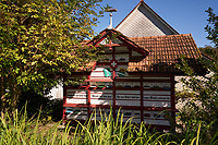 "A traditional chalet apiary at the Bregensdorf farm. First cited in 1315, the farm has housed basket hives for centuries. Beekeeping is a complementary activity for the Fisch family.<br /> ""Take the example of the hardworking bees, it is only through work that benediction comes"".<br /> Un rucher châlet traditionnel à la ferme de Bregensdorf. Mentionée pour la première fois en 1315, la ferme a abrité des ruches panniers pendant des siècles. L'apiculture est un complément pour la famille Fisch.<br /> « Prends l'exemple des abeilles laborieuses, c´est seulement par le travail que vient la bénédiction »."