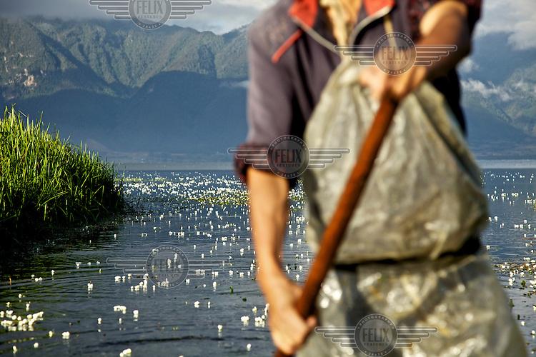 Fisherman Peng (surname) Guang Fa, 42, paddles his boat on Lugu Hu Lake. /Felix Features