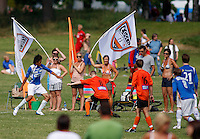 Parents and supportsers line a football field during a match. Norway Cup is the worlds largest football tournament, in 2008 bringing together 30.000 children from all over the world, aged 10 to 19. They make up 1386 teams playing a total of 4400 matches during the week they play. The tournament is played on a big grass field just outside the center of Oslo, Norway.
