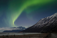 winter landscape shows Northern Lights (Aurora Borealis) in sky above moonlight on the Chugach Mountains along Turnagain Arm and Seward Highway January 2014
