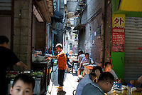 People eat at a small alley restaurant on Shibati (18 steps), a street made mostly of stairs, in Chongqing's central Yuzhong District. The neighborhood will be demolished for new development in October 2014, and the owner of the restaurant, which does not have a name, said that most of his customers are now construction and demolition workers because meal prices are so inexpensive, generally 7 RMB for a plate.