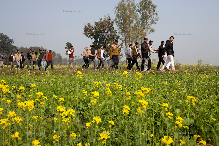 "Minister of Legislative Assembly, Ritesh Pandey, 30, walks through mustard fields as he campaigns door-to-door in rural villages with a crowd of supporters chanting slogans such as ""long live Ritesh Pandey"" and ""press the button, decide the elephant (symbol)"" in Ajanpara, Ambedkar Nagar, Uttar Pradesh, India, on 21st January, 2012. Returning 1.5 years ago after almost 10 years abroad, Pandey is contesting on behalf of the Bahujan Samaj Party (BSP), a party that is based on its appeal to Dalit (the lowest Hindu caste) voters. Party leader Mayawati, herself a Dalit, has recently been giving out more tickets to muslims and high caste candidates in an attempt to woo a larger spectrum of voters in Uttar Pradesh, a Bellwether state. Photo by Suzanne Lee for The National (online byline: Photo by Szu for The National)"