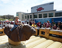 NWA Democrat-Gazette/ANDY SHUPE<br /> Aidan Turner, 5, of Elkins smiles Saturday, April 6, 2019, as he rides a mechanical bull during the annual HogFest fan celebration prior to the Razorbacks' spring game in Razorback Stadium in Fayetteville. Visit nwadg.com/photos to see more photographs from the game.