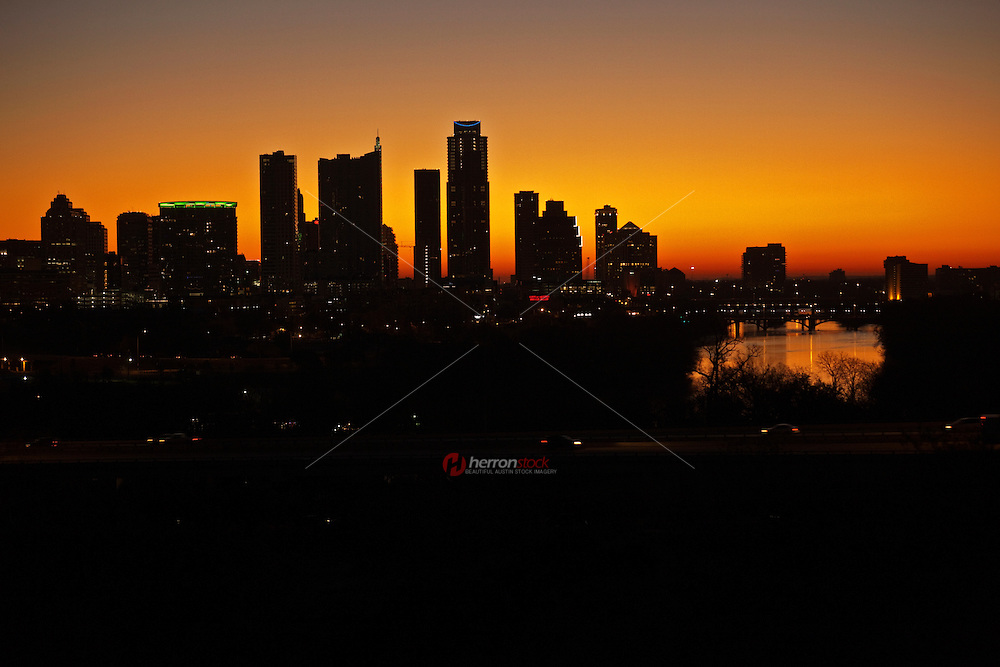 A vivid sunrise overshadows the Austin texas city skyline silhouette and Colorado River