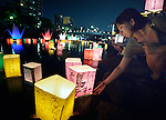A woman sets a floating candle lantern on the river on August 6, 2015, in Hiroshima, Japan. The lanterns, thousands of which were launched on the 70th anniversary of the atomic bombing of the city, carried handmade messages and drawings, conveying each person's prayers for peace and comfort for the victims of the violence.