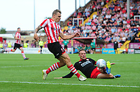 Lincoln City's Harry Anderson crosses the ball despite the attentions of Swindon Town's Matthew Taylor<br /> <br /> Photographer Chris Vaughan/CameraSport<br /> <br /> The EFL Sky Bet League Two - Lincoln City v Swindon Town - Saturday 11th August 2018 - Sincil Bank - Lincoln<br /> <br /> World Copyright &copy; 2018 CameraSport. All rights reserved. 43 Linden Ave. Countesthorpe. Leicester. England. LE8 5PG - Tel: +44 (0) 116 277 4147 - admin@camerasport.com - www.camerasport.com