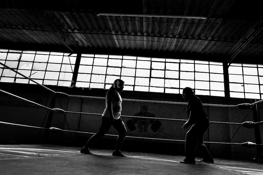 "A female Lucha libre wrestler trains with her coach at a combat sports gym in Mexico City, Mexico, 29 April 2011. Lucha libre, literally ""free fight"" in Spanish, is a unique Mexican sporting event and cultural phenomenon. Based on aerial acrobatics, rapid holds and the use of mysterious masks, Lucha libre features the wrestlers as fictional characters (Good vs. Evil). Women wrestlers, known as luchadoras, often wear bright shiny leotards, black pantyhose or other provocative costumes. Given the popularity of Lucha libre in Mexico, many wrestlers have reached the cult status, showing up in movies or TV shows. However, almost all female fighters are amateur part-time wrestlers or housewives. Passing through the dirty remote areas in the peripheries, listening to the obscene screams from the mainly male audience, these no-name luchadoras fight straight on the street and charge about 10 US dollars for a show. Still, most of the young luchadoras train hard and wrestle virtually anywhere dreaming to escape from the poverty and to become a star worshipped by the modern Mexican society."