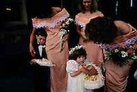 A ring bearer, flower girl and bridesmaids huddle together on a chilly rainy day before a wedding begins outside the Century Inn in Scenery Hill, PA. The historic inn is the oldest that is still being run located on the old National Pike.