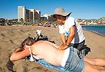 Massage on  beach and people sunbathing, Playa de Malaguera, Malaga, Spain