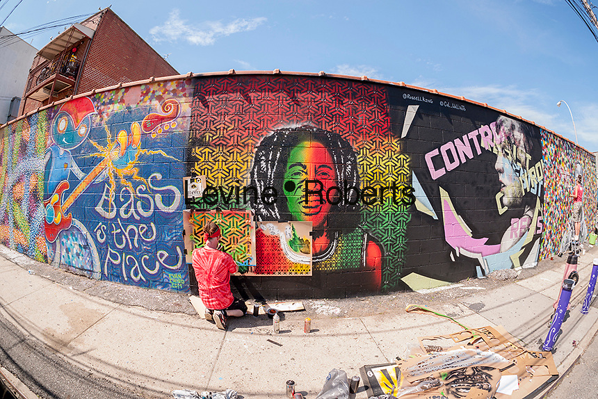 Street artist Eyez working at the Welling Court Mural Project in the Astoria neighborhood of Queens in New York on Saturday, June 13, 2015. The annual neighborhood event decorates walls in this industrial part of Astoria. The project is crowd-funded and emerging street artists work side by side with established stars.  (© Richard B. Levine)