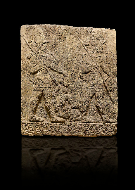 Hittite sculpted Orthostats panel of Long Wall Limestone, Karkamıs, (Kargamıs), Carchemish (Karkemish), 900-700 B.C. Soldiers. Anatolian Civilisations Museum, Ankara, Turkey<br /> <br /> Figure of two helmeted warriors. They have their shield in their back and their spear in their hand. The prisoner in their front is depicted small. A human head is depicted in the left hand of the warrior in the front. The warrior at the rear holds the prisoners sitting on his lap from his hair. Below this figure, which was described small, lies yet another small human figure. <br /> <br /> On a black background.