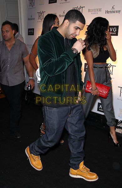 DRAKE (Aubrey Drake Graham).Drake celebrates official After-Party at Tryst Nightclub at the Wynn Las Vegas, Las Vegas, Nevada, USA. .November 6th, 2010.full length green velvet jeans denim jacket black top tan boots shoes walking side profile hand.CAP/ADM/MJT.© MJT/AdMedia/Capital Pictures.