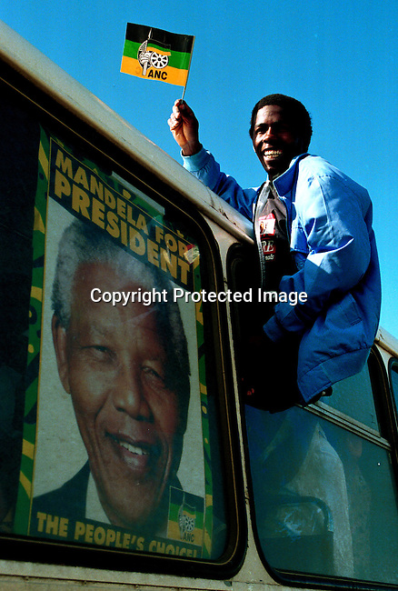 DIELECT00074.Polotics. Elections. An ANC (African National Congress) supporter at a election rally a few days before the historic democratic election in South Africa on April 27, 1994; poster in bus window with man holding flag..©Per-Anders Pettersson/iAfrika Photos