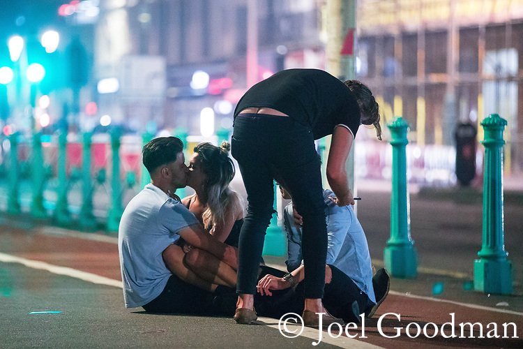 © Joel Goodman - 07973 332324. 26/09/2017. Brighton, UK. A couple kiss as a group sit together on the pavement on Brighton Promenade . Revellers at the end of a night out during Freshers week , when university students traditionally enjoy the bars and clubs during their first nights out in a new city . Photo credit : Joel Goodman