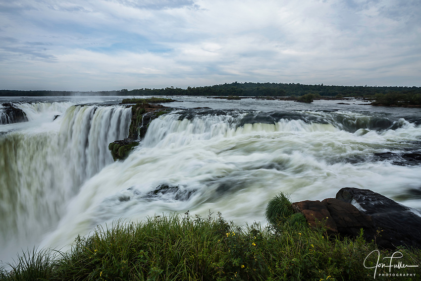 The water of the Iguazu River falls over the precipice of the Garganta del Diablo or the Devil's Throat Waterfall in Iguazu Falls National Park in both Argentina and Brazil.  Both parks are UNESCO World Heritage Sites.