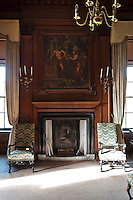 A neo-classical painting framed in the wood panelling above a fireplace
