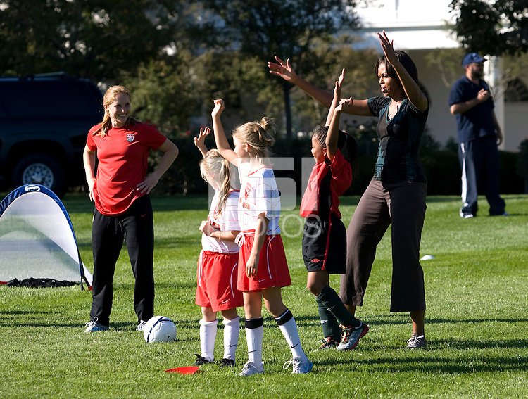 Michelle Obama celebrates winning a short competition with players from Soccer Sisters United and Prince William Courage Soccer Club during a Lets Move! soccer clinic held on the South Lawn of the White House.  Let's Move! was started by Mrs. Obama as a way to promote a healthier lifestyle in children across the country.