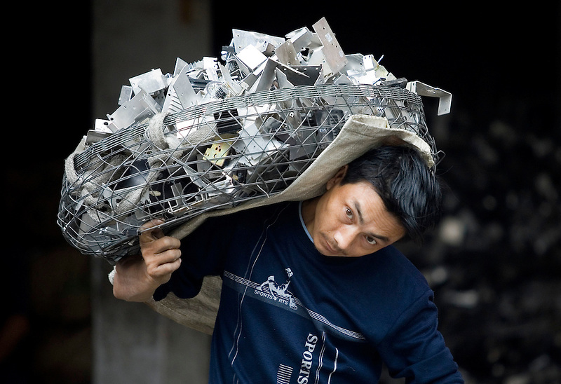 A migrant worker carries a load of scrap metal or recycling extracted from illegally imported electronic trash in Guiyu, China. . E-trash plagues China. Each year, between 20 and 50 million tons of electronic waste is generated globally. Most of it winds up in the developing world...