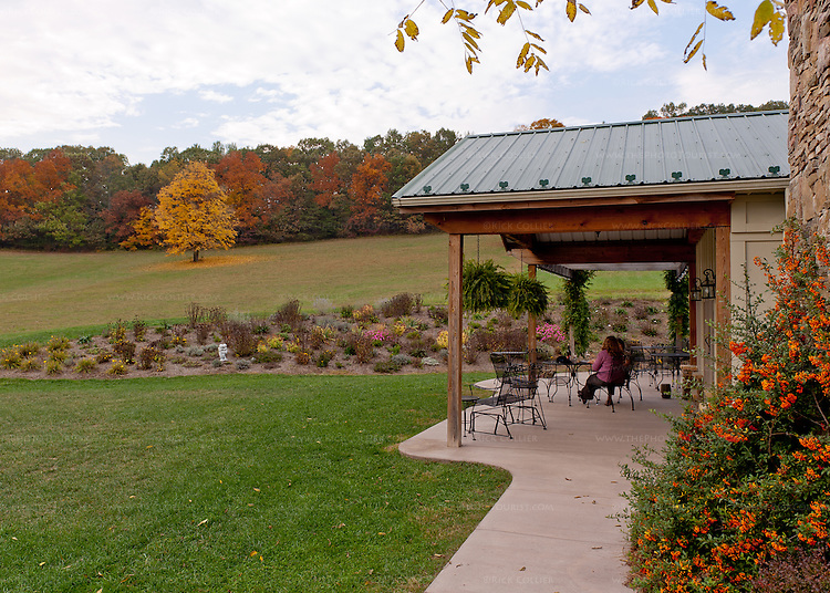 Visitors relax and enjoy wine and the view of fields and autumn trees, on the patio outside the tasting room at West Wind Farm Vineyard and Winery.
