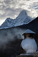 The peak of Ama Dablam towers above an incense burner in the town of Deboche on the trail to Everest Base Camp in the Himalayan mountains of Nepal.