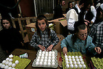 Boys with traditionally untrimmed locks, or peot, sort eggs to be distributed to the needy in the ultra-Orthodox Jewish neighborhood of Mea Shearim, Jerusalem, April 6, 2009. In the days leading up to the Passover holiday, observant Jews purge their houses of bread and other leavened foods, which are not consumed during the eight-day holiday commemorating the Israelites' Exodus from Egypt. The custom culminates in the symbolic burning of crumbs. Photo by: Daniel Bar On/JINI