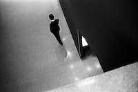 The silhouette of a man walking in a building hallway, seen from above