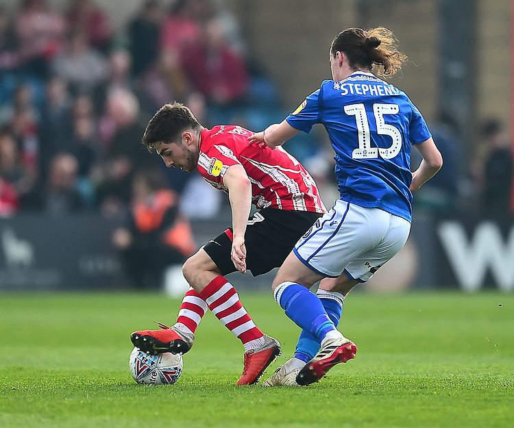 Lincoln City's Tom Pett shields the ball from Macclesfield Town's Ben Stephens<br /> <br /> Photographer Andrew Vaughan/CameraSport<br /> <br /> The EFL Sky Bet League Two - Lincoln City v Macclesfield Town - Saturday 30th March 2019 - Sincil Bank - Lincoln<br /> <br /> World Copyright © 2019 CameraSport. All rights reserved. 43 Linden Ave. Countesthorpe. Leicester. England. LE8 5PG - Tel: +44 (0) 116 277 4147 - admin@camerasport.com - www.camerasport.com