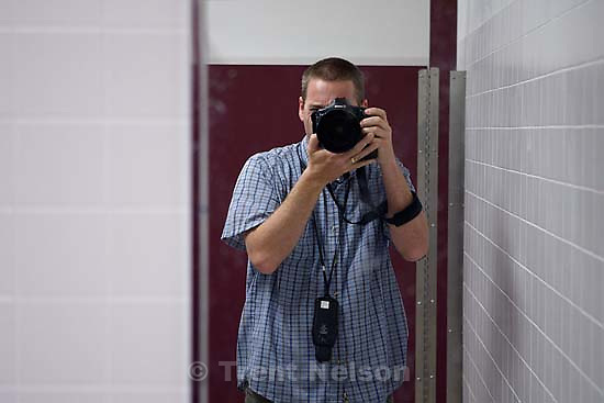 trent nelson in mirror at East Carbon High School. The final class to graduate before the school was closed and students were transfered to the high school in Price, Utah.; 5.25.2005<br />