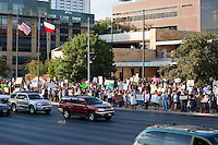 Occupy Austin protesters shower the traffic passing Austin City Hall with their concerns