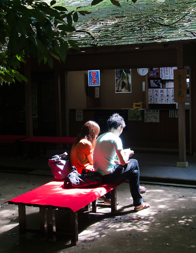 Couple sitting and enjoying food at Todoroki Valley Tea house in Tokyo with nice light.