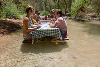 8/2/09 Havasupai-- Lisa Brown, 20, of Ohio, left, and Ruth McDaniel, of California, play poker while sitting at a picnic table in the water. The group was camping at the Havasupai campground. (Pat Shannahan/ The Arizona Republic)