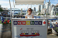 Young woman selling tickets for the aquabus water taxi, Granville Island, Vancouver, British Columbia, Canada