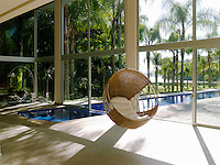 A woven pod chair hangs in the large living area which is flooded with sunlight