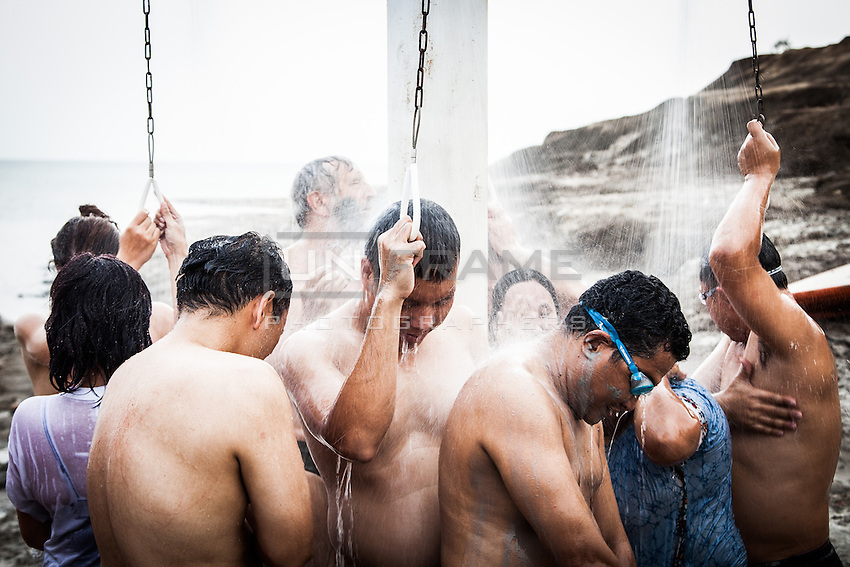Bathers pictured as they take showers following a bathe in the waters of the Dead Sea. Palestinian Territory.