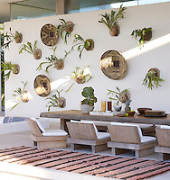 In the pool cabana, the teak table and chairs were designed by Bonetti Kozerski Studio; Zambian baskets and staghorn ferns hang on the wall, and the rug is Moroccan