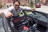 Roman Gomez removes the roof from his mother's electric Tesla Roadster at Bayfront, Naples, Florida, USA, July 19, 2012. Photo by Debi Pittman Wilkey, CoastalLife.com.