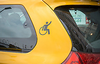 "An accessible symbol on a yellow cab stopping at the Taxis For All Campaign protest in front of Uber headquarters in West Chelsea in New York on Thursday, July 30, 2015. The protesters had a ""roll-in"" calling on the company to stop discriminating against the disabled by requiring handicapped accessible vehicles. Out of 20,777 Uber cars on the road not one of them is wheelchair accessible. (© Richard B. Levine)"