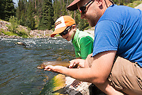 An young boy admires his first trout on Hyalite Creek near Bozeman, Montana.
